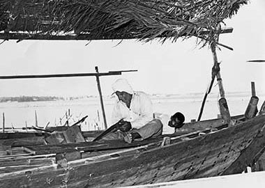 A shipwright sawing a plank on a traditional boat