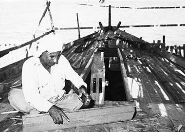 A shipwright using an adze to trim a timber
