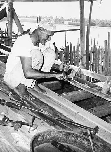 A shipwright using a bow drill