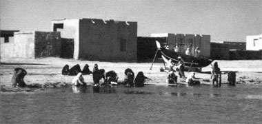 Women washing clothes in the sea at al-Khor