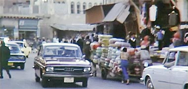 Porters moving a heavy load through the suq, 1968 – image developed from a video with permission from glasney on YouTube