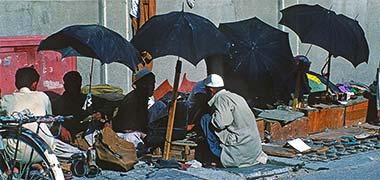 Shoe menders outside the suq's main mosque, April 1972
