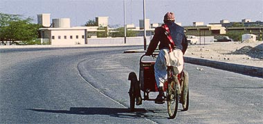 A tricycle being ridden on the 'C' ring road, 1975