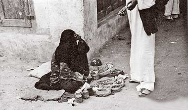 A woman selling small items in the suq in the 1950s – courtesy of Mohammad Naseer